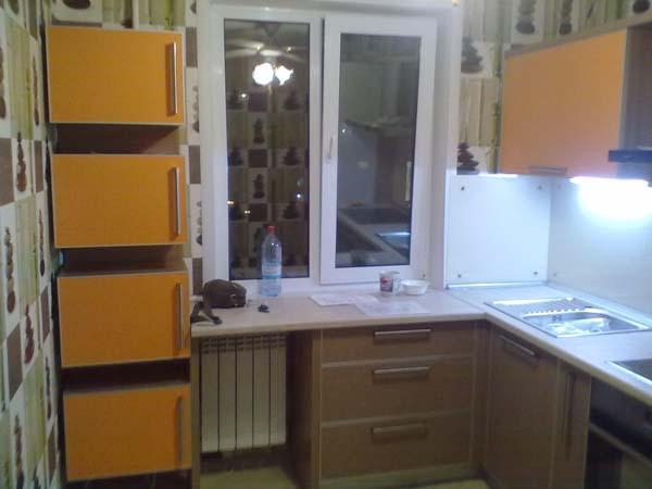 Угловая кухня с оранжевыми навесными шкафчиками